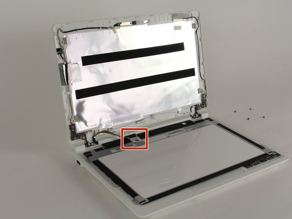 Use tweezers to peel of the sticker securing the cable to the laptop behind the screen.