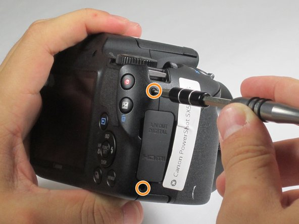 Image 3/3: Remove 4-4 mm screws on the left and right sides of the camera using a Phillips #000 screwdriver.