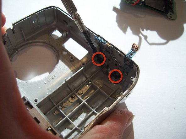 Use a Philips screwdriver to unscrew the two screws that connect the photo button to the outer front casing.