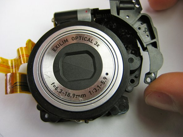 Now that the lens is fully exposed, remove the two phillips screws (4.34 mm) on front of the lens.