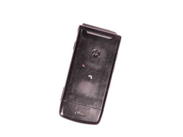 Image 1/2: Push down on the silver tab located at the top center of the back of the Motorola W490 cellphone.