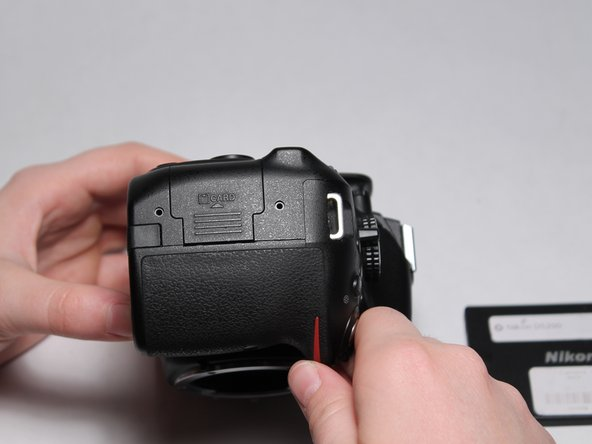 Turn the camera on its side as shown to reveal the SD card door.