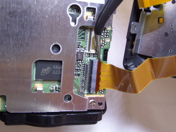 Image 3/3: Pull the wire ribbon towards the back end of the camera.