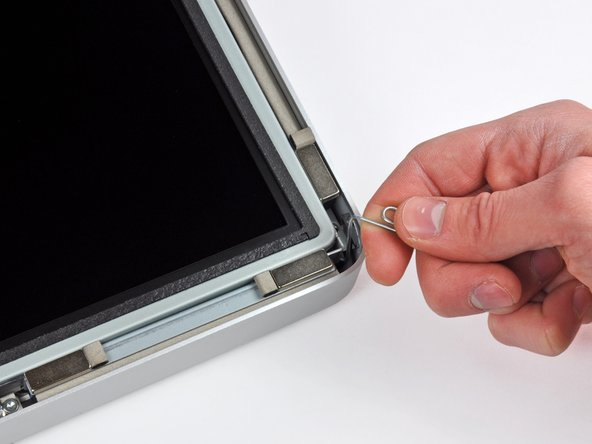 Image 2/3: Due to tight tolerances, you will have to use a thin hooked tool to lift the display out of the outer case. As seen in the first picture, we made one out of a bent paperclip.