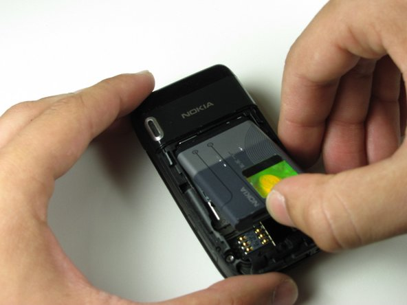 Lever out the battery from the phone using your thumb.