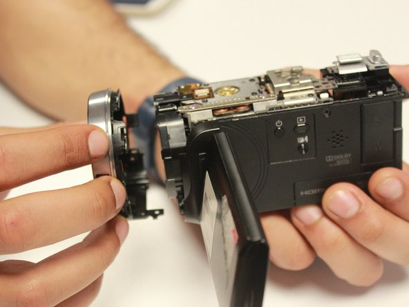 Image 2/2: Keep holding the camera with your right hand then gently remove the lens cover panel with your left hand.