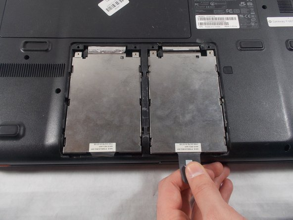Pull the plastic tab as shown to remove the hard drive from the device.