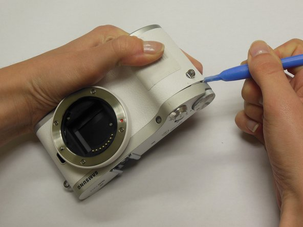 Using a plastic opening tool, carefully remove the top panel of the camera.