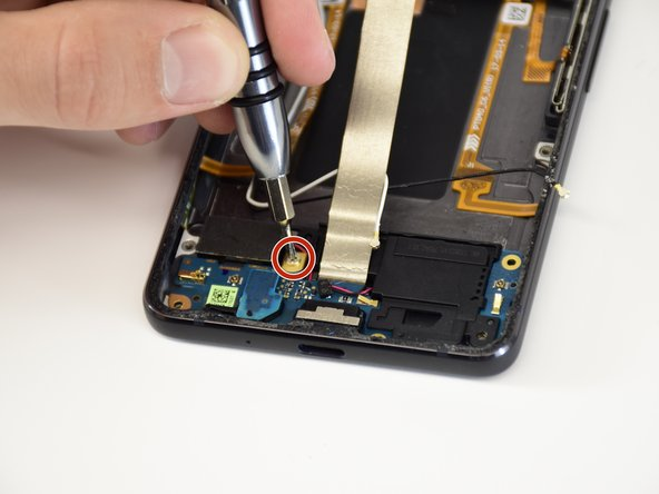 Remove the J000 2.5mm screw by turning the screwdriver counterclockwise.