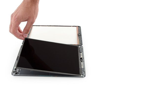 Use the flat end of a spudger to pry the LCD out of its recess just enough to grab it with your fingers.