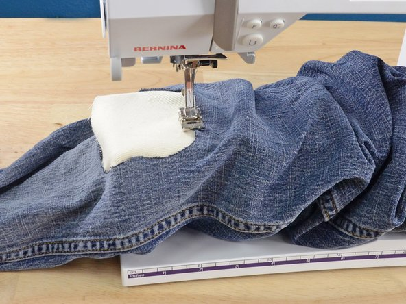 Slide the pant leg with the patch over the arm of the sewing machine.