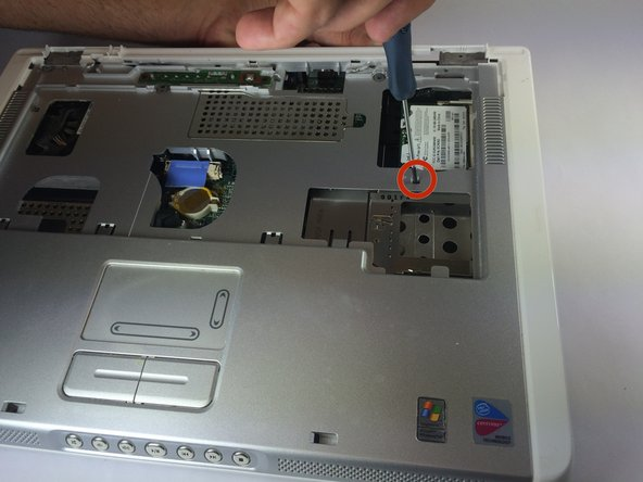 Remove two 4 mm Philips #00 screws that connect top of laptop to base..