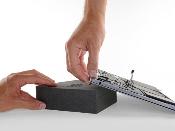 To separate the center battery cell, raise the back edge of the MacBook Pro and prop it up on a foam block or book, so that the adhesive remover will flow away from the logic board.