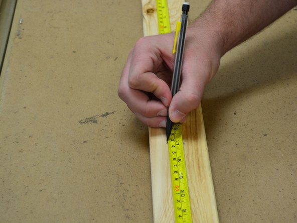 Using the tape measure, measure the distance between the two sides of the dresser frame and then cut a beam of wood to fit these specifications.