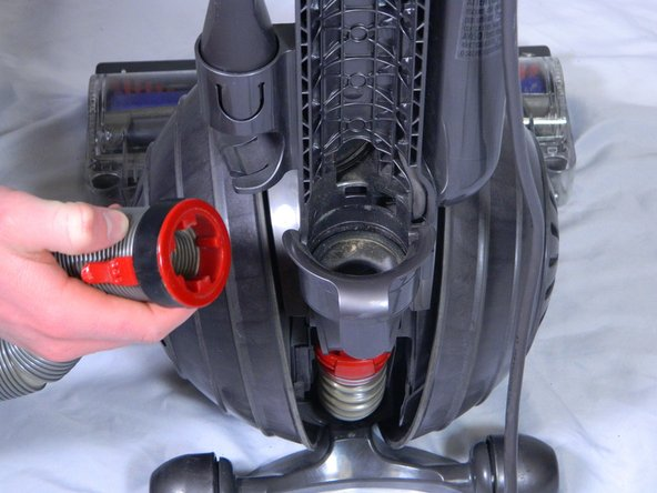 Lift up the red tab with the screwdriver while simultaneously pulling on the back hose.