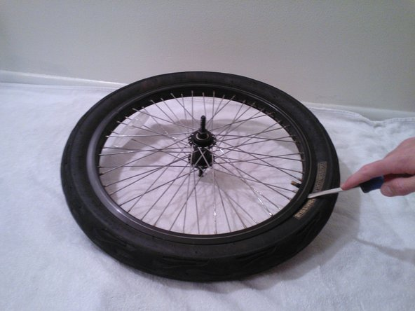 Wedge a screwdriver between the tire and the rim to pry it over the tire over the rim as shown. Part of the tire should now be on top of the rim.