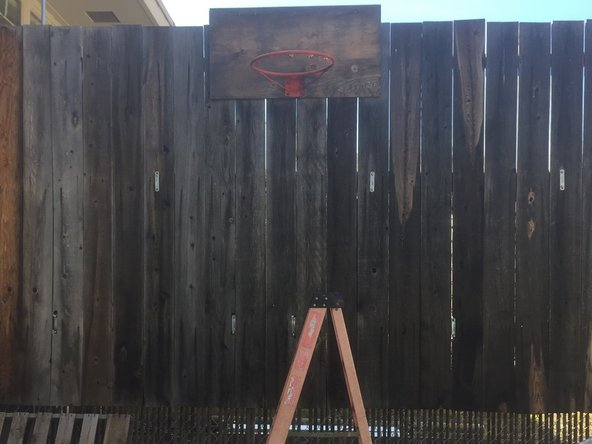 Set up a ladder below the basketball rim.