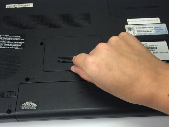Insert something thin, such as your fingernail or a credit card, into the slot at the bottom edge of the RAM panel.