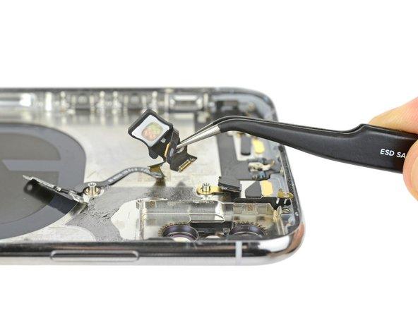También quitamos el otro cable de multi función de la parte de arribe del teléfono. Este ensamblaje es hogar al flash de cuatro LED True Tone, y al botón de inicio, igual como a los iPhones del pasado.