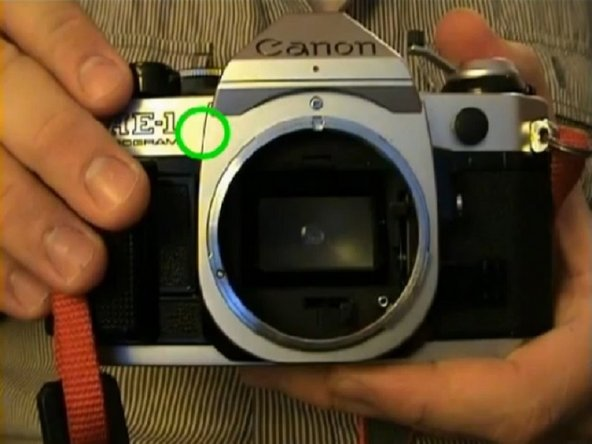 "Remove the front beauty piece from the camera. The screws are in front below the word ""Canon"", on the left, on the right and...."