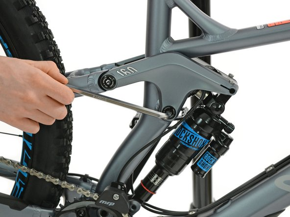 Use a 6mm allen key to loosen the shaft of the rocker bearing on the right side of the frame.