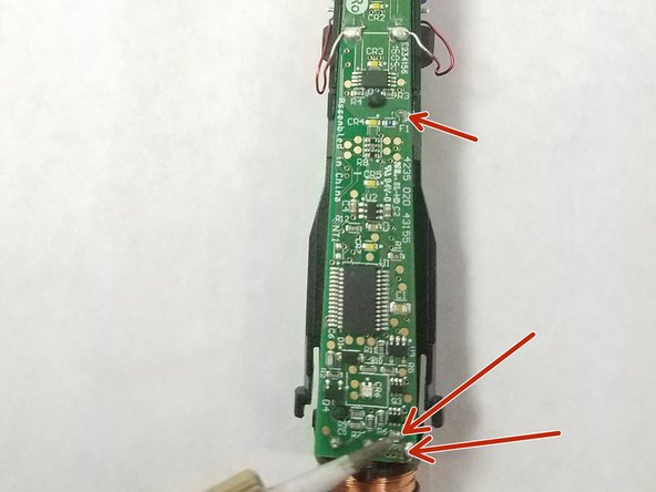 Using a soldering iron, remove the solder from the three marked spots.