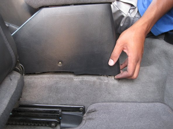 Grab the bottom of the rear portion of the console and lift up and away from the front of the car.