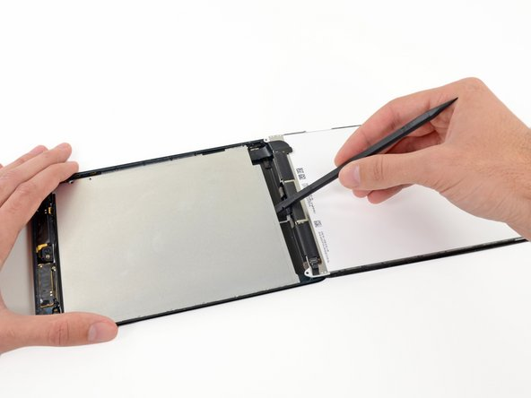 Insert the flat end of a spudger underneath the center of the LCD shield plate from the bottom end of the iPad.