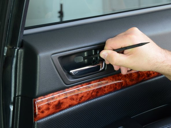 Use a spudger or a flat-blade screwdriver to unlatch the plastic screw cover residing within the door pull handle.