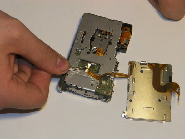 Image 3/3: The screen should now be separate from the camera body. Be careful not to harm the connectors on the lens so it will reconnect successfully.