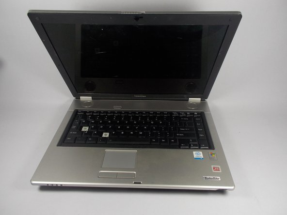 Open laptop by sliding the front tab to the right and lifting the screen.