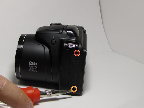 Remove the 5 mm Phillips #000 screw located on the upper left side of the camera