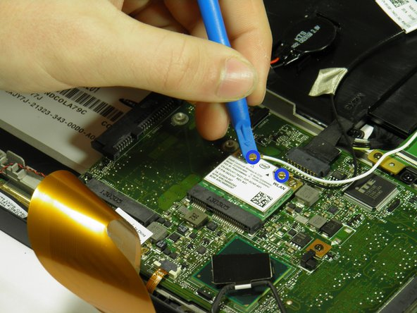 Use the plastic opening tool's angled edge to remove the black and white wires connected to the wireless WLAN card.