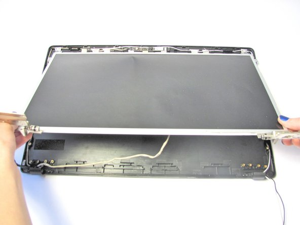 Once the screws are removed, lift up the LCD to expose the wire connecting the back bezel to the LCD.