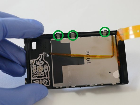 Release the 3 metal clips from the rear cover and remove the LCD