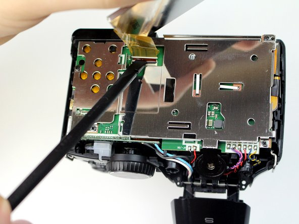 Gently tilt the LCD screen toward the bottom of the camera and use a spudger to flip the lock for the ZIF cable attached to the LCD.