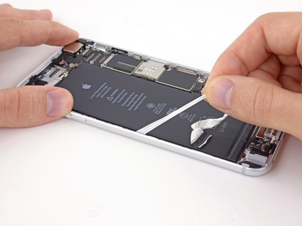 When you feel increased resistance from the adhesive strip, pull it gently around the lower left corner of the battery.