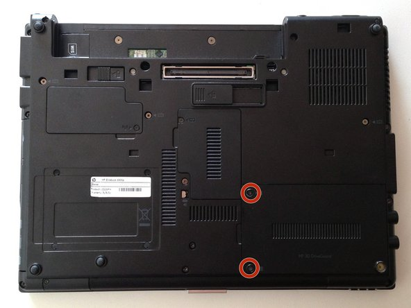 With the bottom of the laptop facing up and the front toward you locate and loosen the two M2.0×5.0 captive screws holding the hard drive bay cover closed.