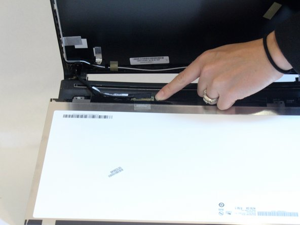 Gently lay the screen on the keyboard and remove the tape over the connection. You can then disconnect the screen.