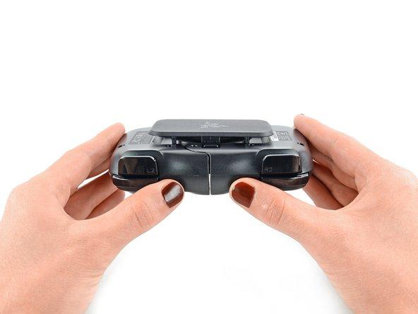 Deux loquets de verrouillage sur le dos de la Kishi maintiennent les deux moitiés de l'appareil et permettent de compacter la manette lorsqu'il n'y a pas de téléphone dedans.