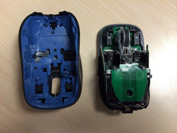 Lift the rear of the top case of the mouse and slide forward. It should be fairly easy to release.
