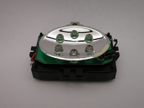 The inner electronics of module of the front panel includes a parabolic mirror, circuit board, and battery holder.