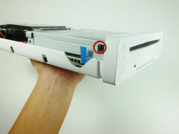 Image 1/2: On each side of the console, remove the 3.5mm Phillips #0 screw connecting the DVD drive to the faceplate.