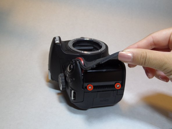 Lift the rubber grip using a plastic opening tool to locate and remove the two screws underneath.