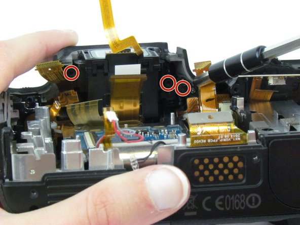Use the Phillips #00 screwdriver to remove the three black 3.8 mm screws below the viewfinder.