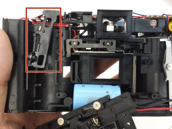 Lift the button mechanism up carefully, removing the spring at the top of the mechanism from where it is attached to the camera body.