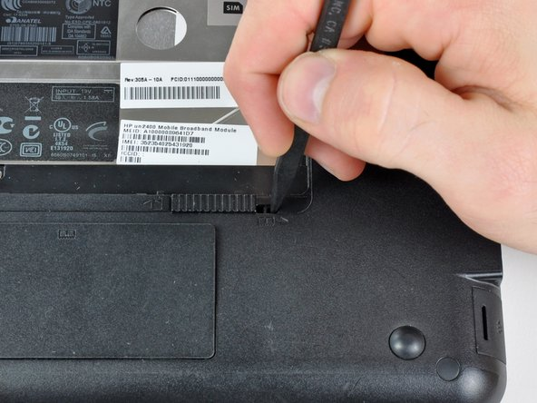 Use the tip of a spudger to slide the RAM compartment cover release latch away from the center of the computer.