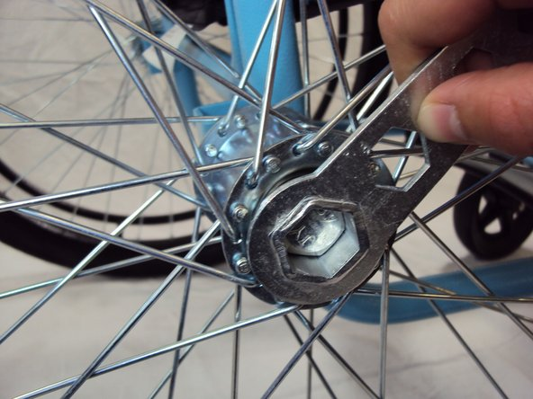 Image 2/3: Remove the axle bolt from hole and remove the wheel from the wheelchair.