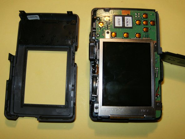 Image 1/3: Gently remove the LCD from the holder and just flip it to the side. Do not remove it yet. You will have to loosen the clip on the connector. Use your fingernails to move it in the opposite direction from the LCD, this will open it up.