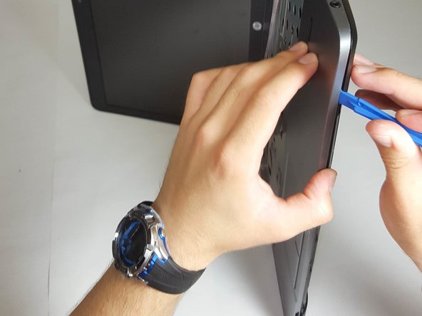 Using a plastic opening tool, slowly and carefully detach the top cover from the bottom frame.